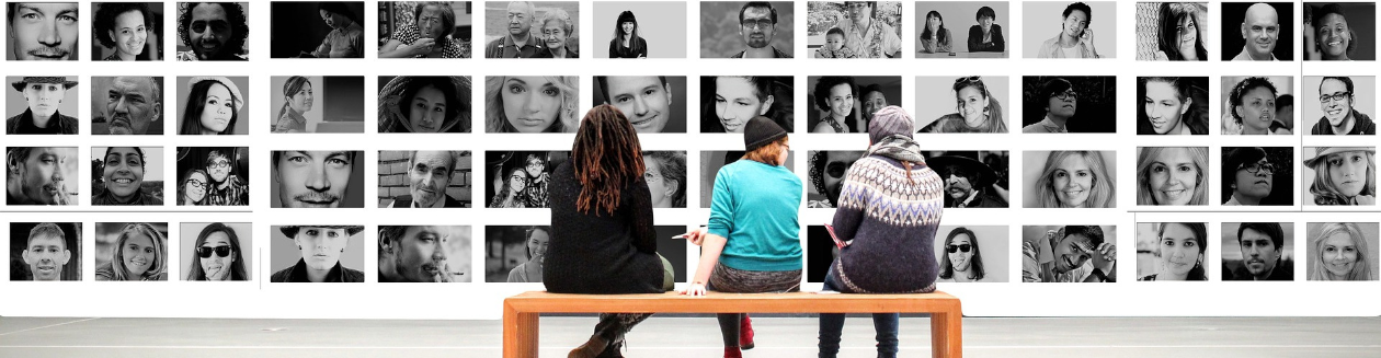 People sitting on bench looking at diverse photos