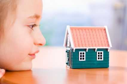 Child playing with toy house
